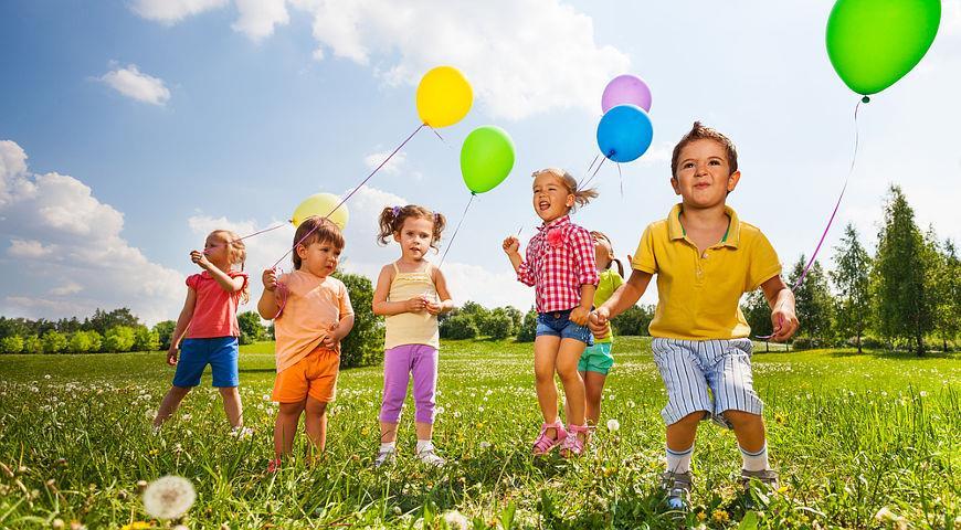 Дети с шариками на траве